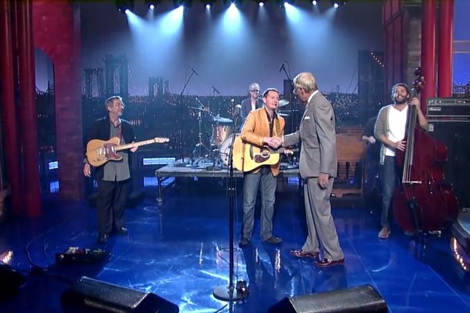 Letterman shaking John's hand.