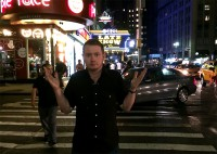 John on the street with the Letterman Show sign behind him.